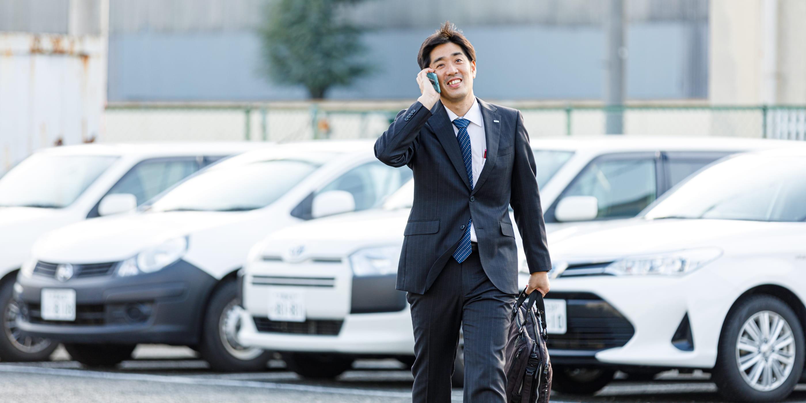 歩きながら電話対応を行う塩澤 功の写真